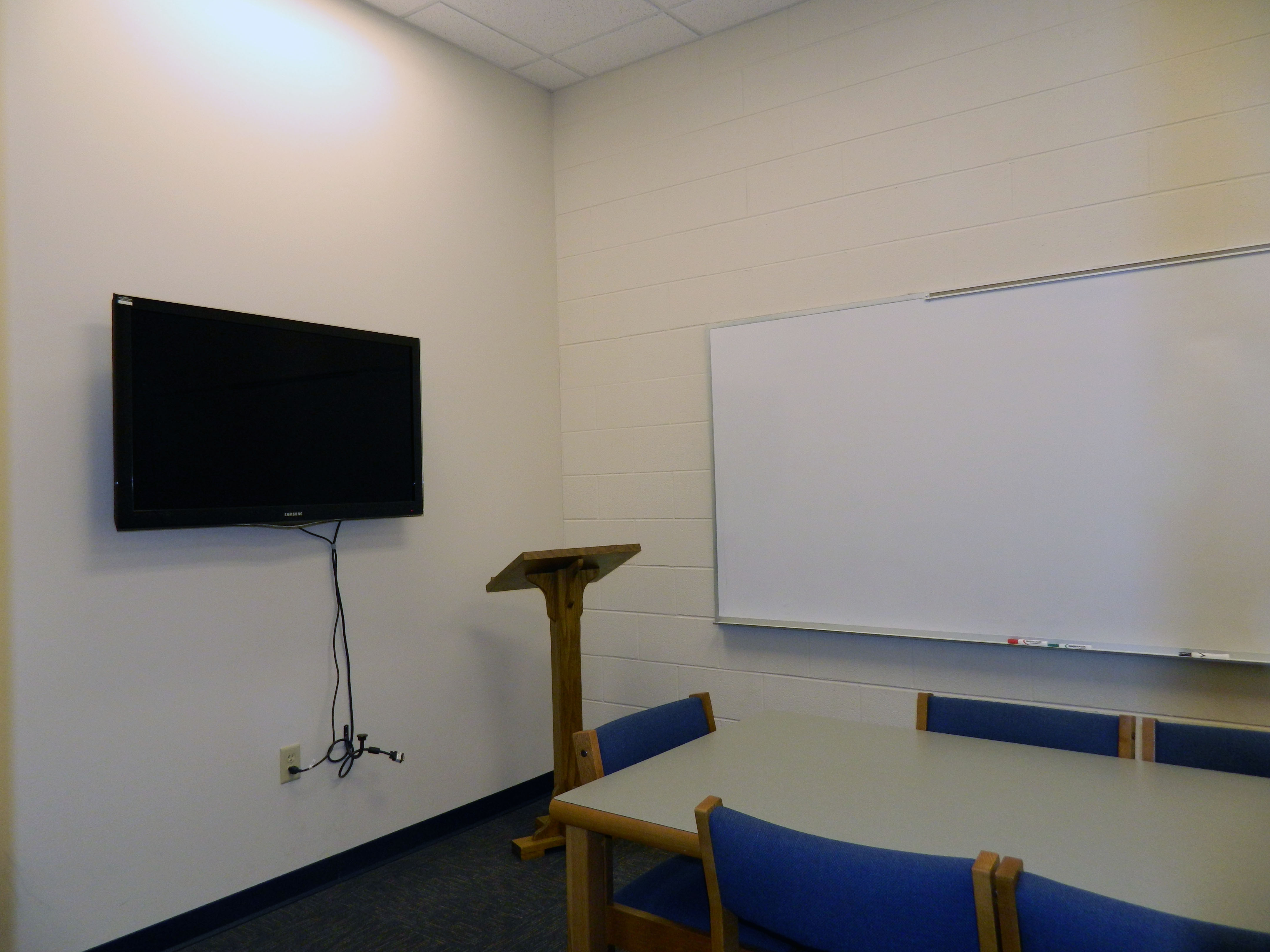Blount County Group Study Room.  The room has a table and six chairs.  It has a dry erase board, podium and a monitor mounted on one wall.