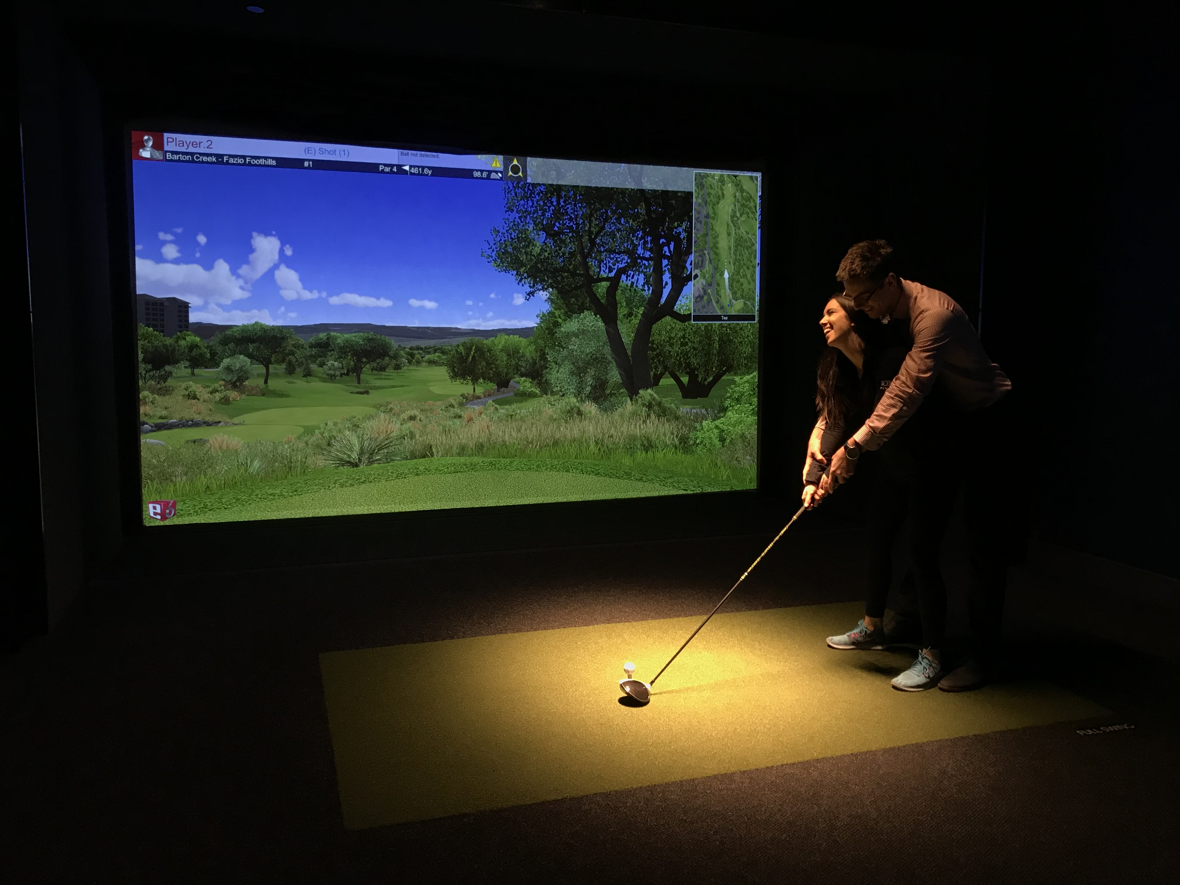 A happy couple enjoying the golf simulator experience at 10XTO.