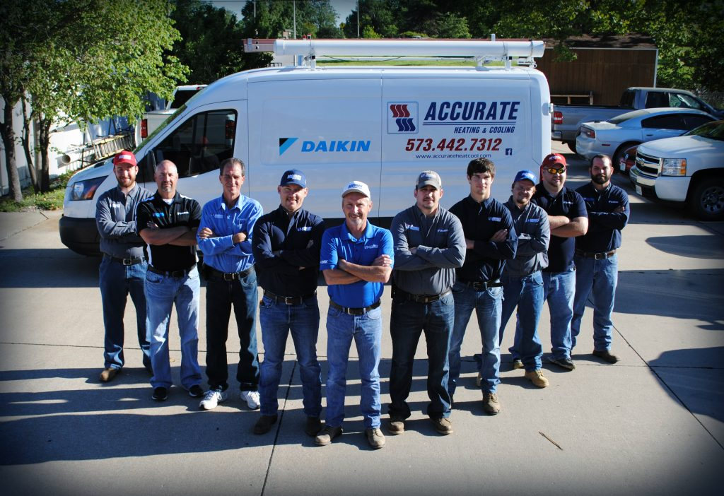 HVAC experts for Accurate Heating and Cooling standing by their van.