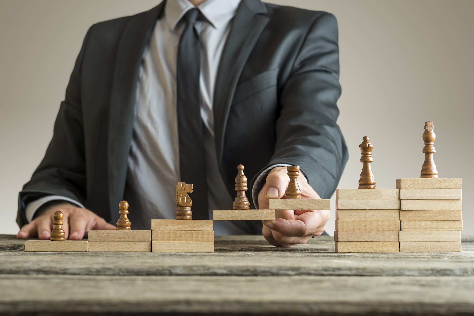 Conceptual image of career management with a businessman forming a bridge of wooden building blocks for chess pieces developing from pawn to king.
