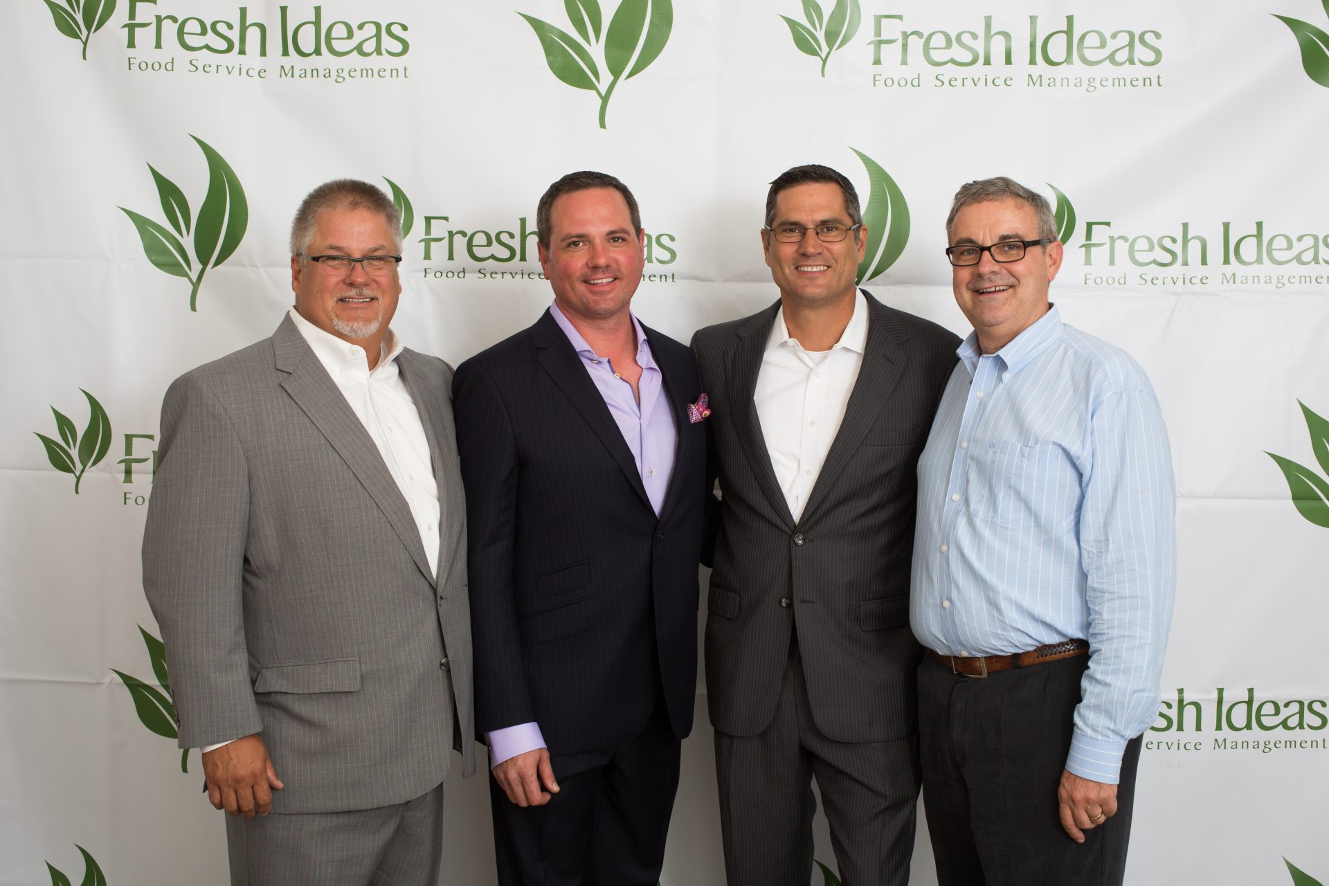 Staff members stand in front of a backdrop at an event sponsored by Fresh Ideas Food Service Managment