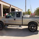 Side view of gray pickup truck at KB Tire & Auto