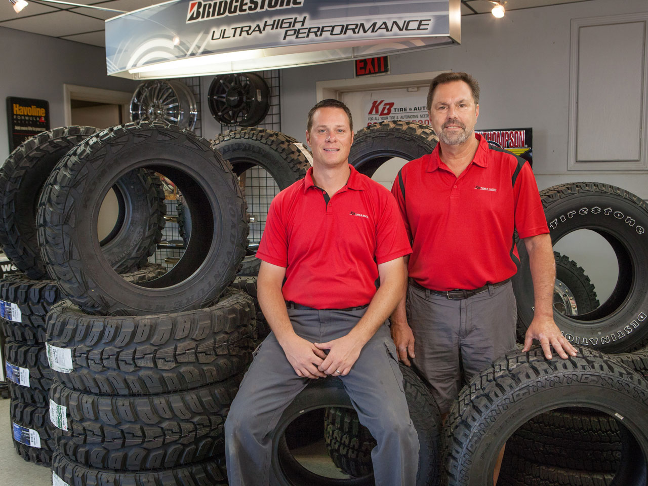 Two men posing in front of tire display at KB Tire & Auto