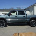 Side view of blue Chevy pickup truck at KB Tires & Auto