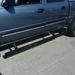 Close up of side nerf step bar on a blue pickup truck