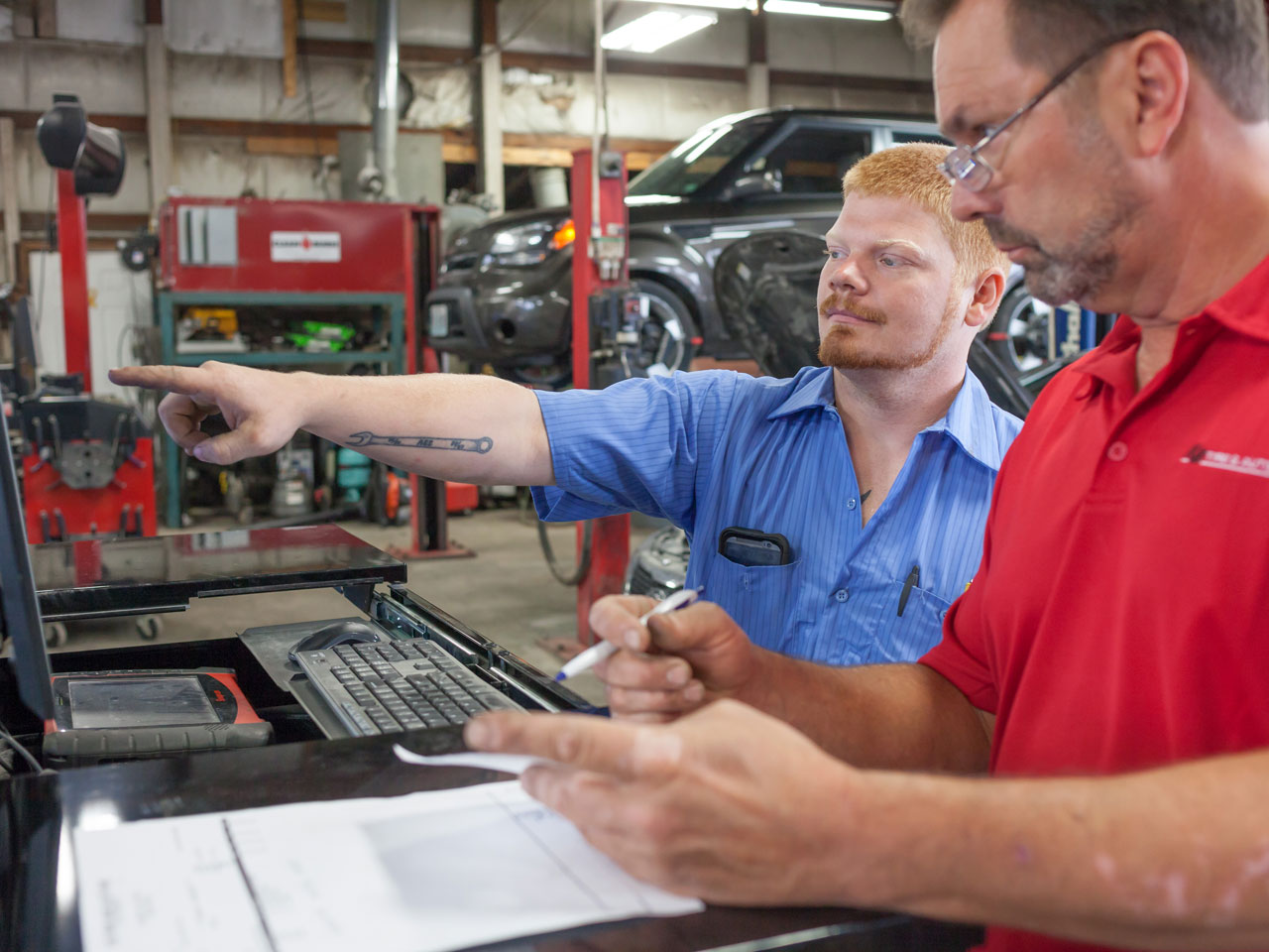 Two automotive technicians performing computerized diagnostics at KB Tire & Auto