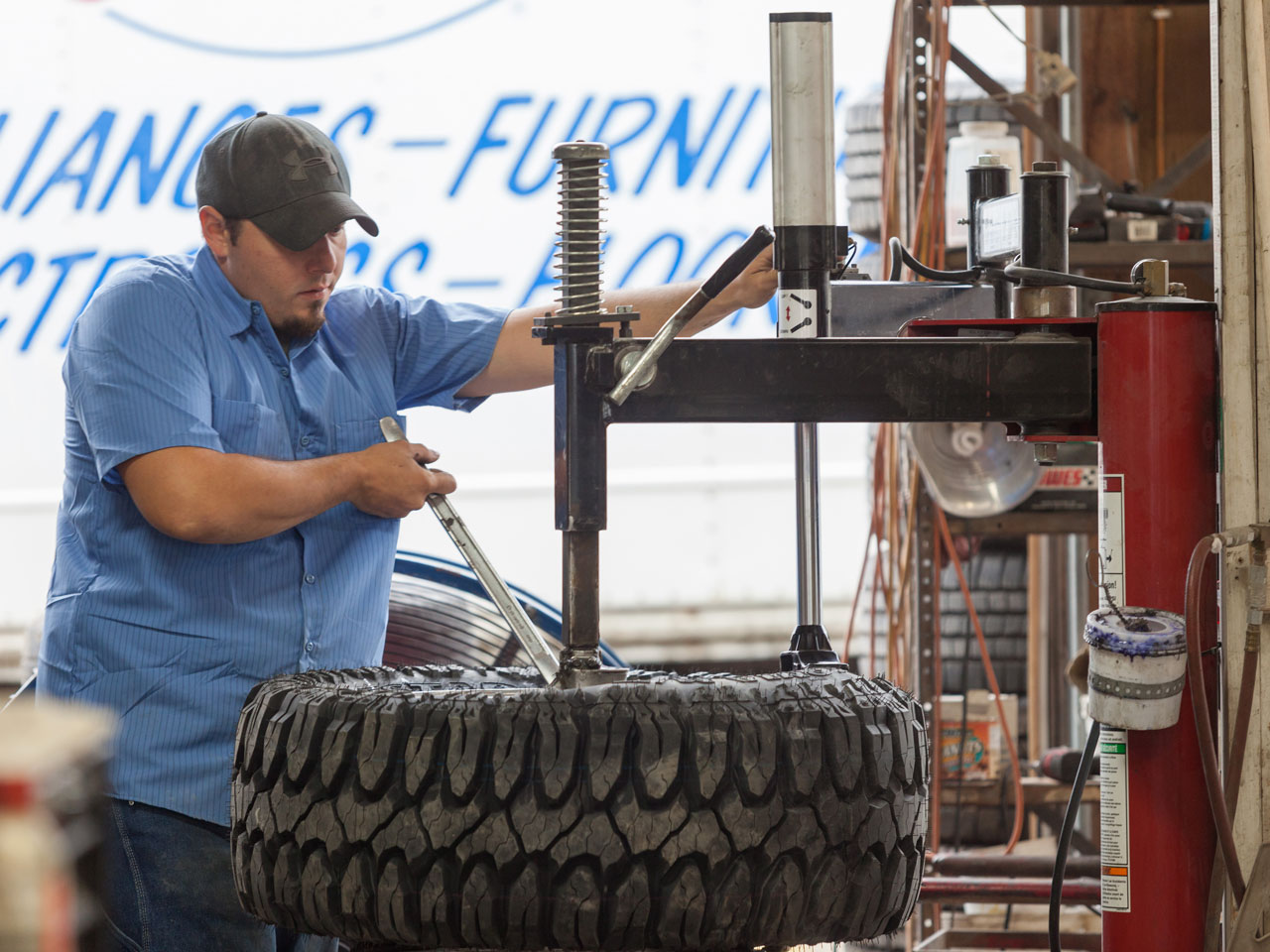 Technician performing a tire rotation on a tire