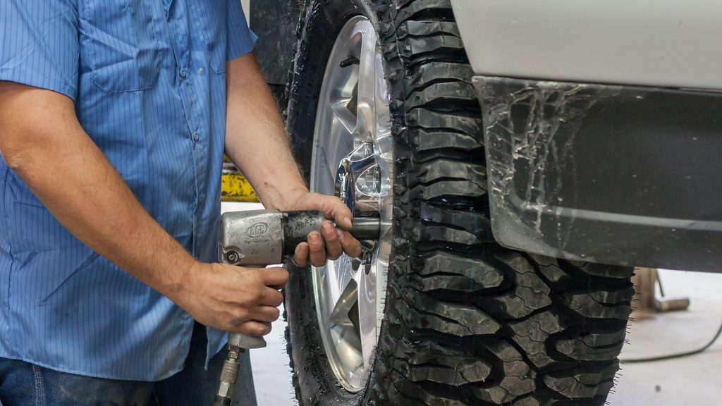 An automotive technicians working on a tire on a vehicle