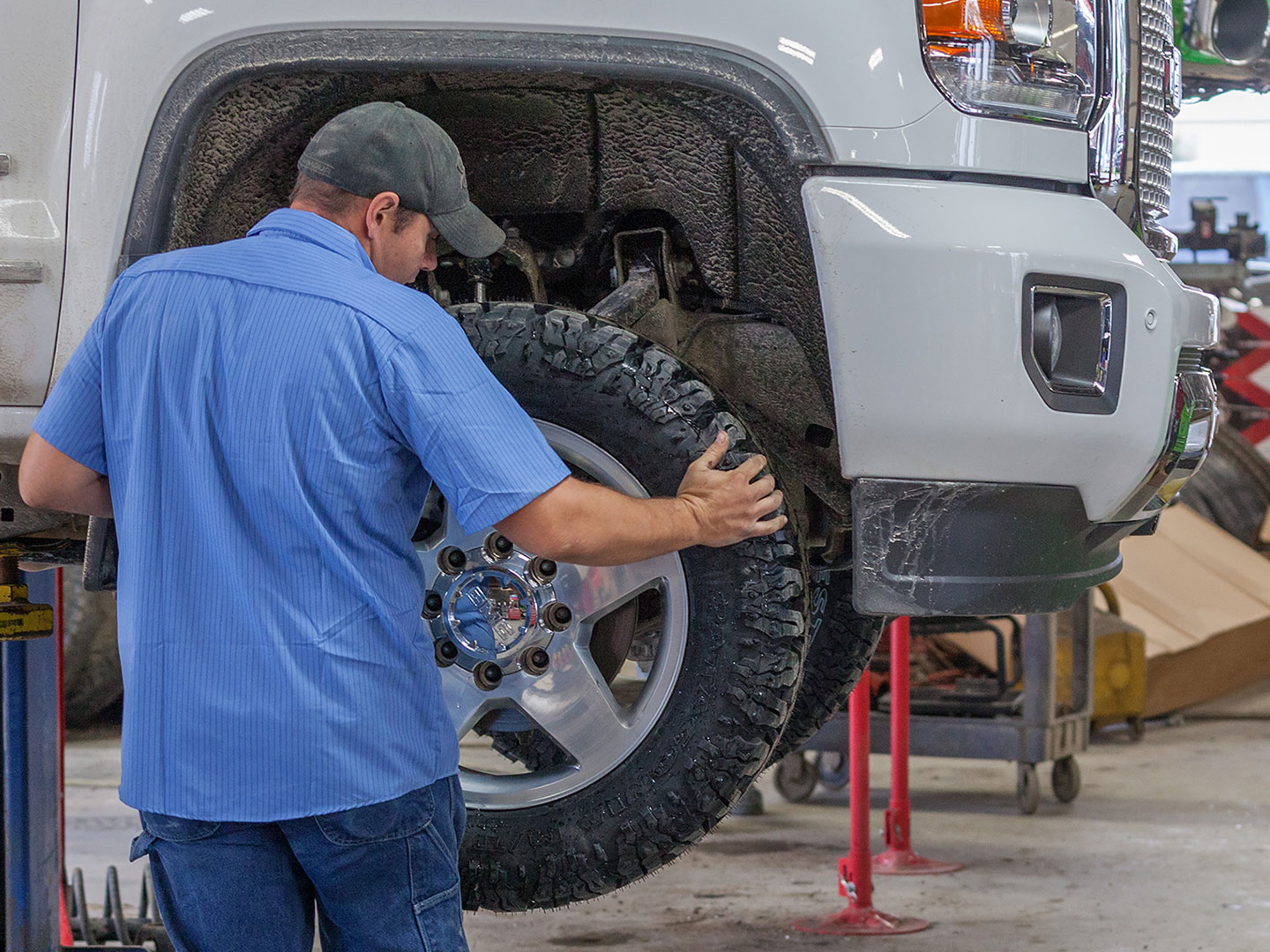 Wheel Balancing - A technician putting a tire back onto a lifted truck
