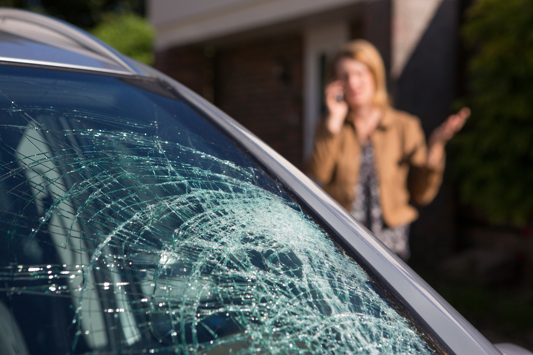 Woman Phoning For Glass Repair Help After Car Windshield Has Broken