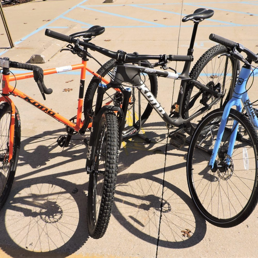 Three different Kona bikes, left orange, middle black, right blue