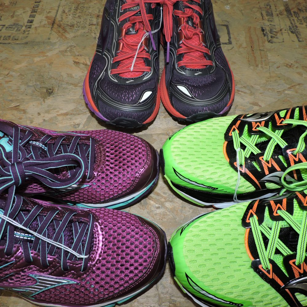three pairs of tennis shoes, purple on left, green on right, black and red in back center