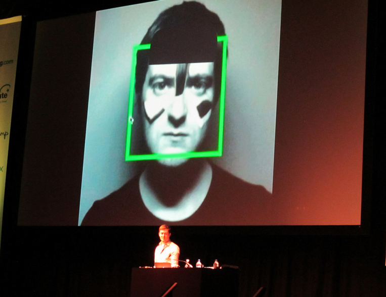 Dan Williams, speaking at dConstruct, 6 September 2013, Brighton, showing himself wearing Adam Harvey's CV Dazzle make-up. Photo CC by Rain Rabbit