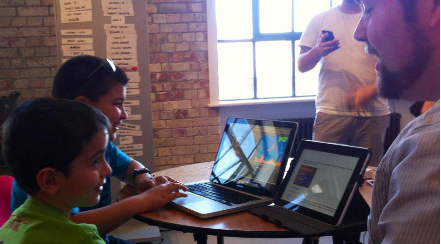 A volunteer teaches children programming at Kids Code Club