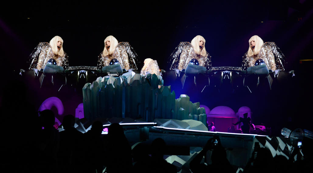 "26 people sit in the Absolut Vodka ARTPOP lounge. Situated in the middle of the arena floor just below Lady Gaga's piano, the lounge features a full-service bar during the show. Two lucky fans get invited to the lounge for ""daring to transform."""