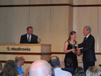 Lindsay Gossack receives her Global Hero award from Dr. Stephen Oesterle, Senior Vice President for Medicine and Technology at Medtronic