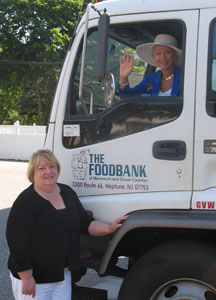 Susan M. Kelly (left), executive director of the FoodBank of Monmouth and Ocean Counties, and Diane S. Turton (in truck), broker of record for Diane Turton, Realtors.