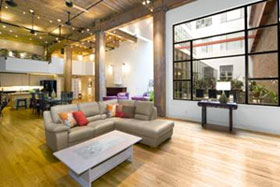 Modern South Beach two-level live/work loft condo features brick and timber details.