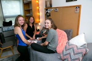 A family helps a new student settle in to her dorm room