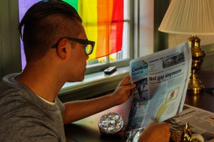 A student reads the newspaper in the Stonewall House on campus