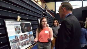 A student presents her project to President Lewis Thayne at Inquiry