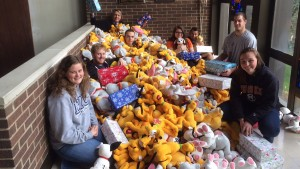 Students pose with stuffed animals for operation chirstmas child