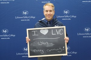Chaplain Paul Fullmer holds a sign during Philanthropy Day