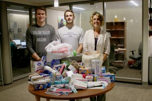 Tristan Ferguson, Nick Tucker, and Jen Liedtka pose with hygiene supplies they've collected for hurricane relief.