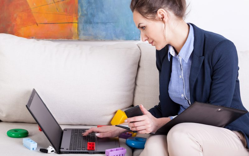 Young mother using laptop to work at home, horizontal