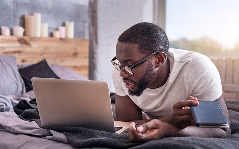 Work at home. African young concentrated man wearing glasses and working while using laptop at home.