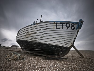 Fine Art Print of Old fishing boat on pebbled beach by Assaf Frank