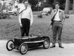 Two men standing by a miniature Sunbeam pedal car Poster Art Print by P.J. Crook