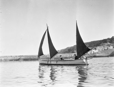 Mounts Bay pilot gig, under sail in Newlyn harbour, setting fore staysail and standing lugs with booms on fore and mizzen masts Poster Art Print by unknown
