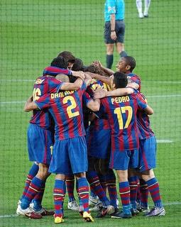 soccer team celebrating in a huddle