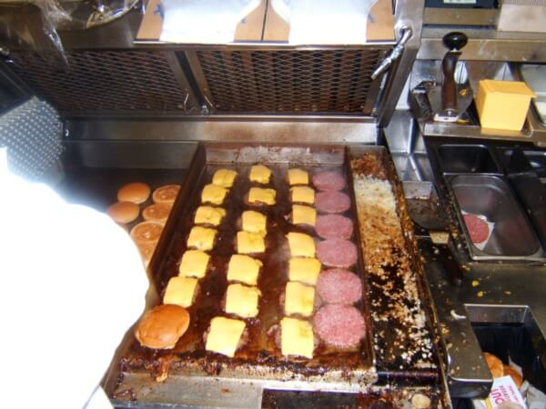 Cheeseburgers frying on a grill