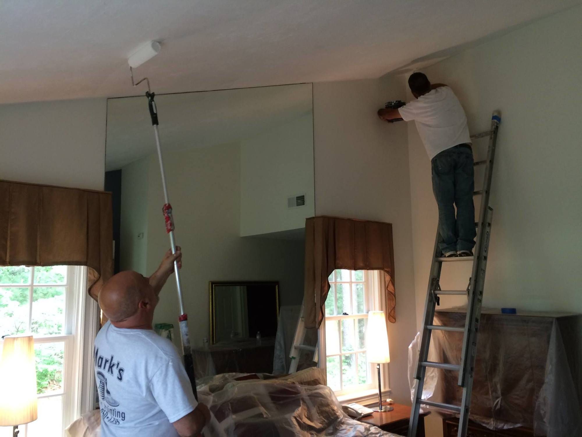 Owner Mark Centola and Mike Brusso painting a customer's ceiling.