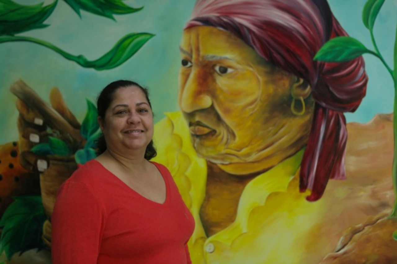 Edda Figueroa poses with a mural in her office, located on Grand Street (Photo by Luke Rafferty)