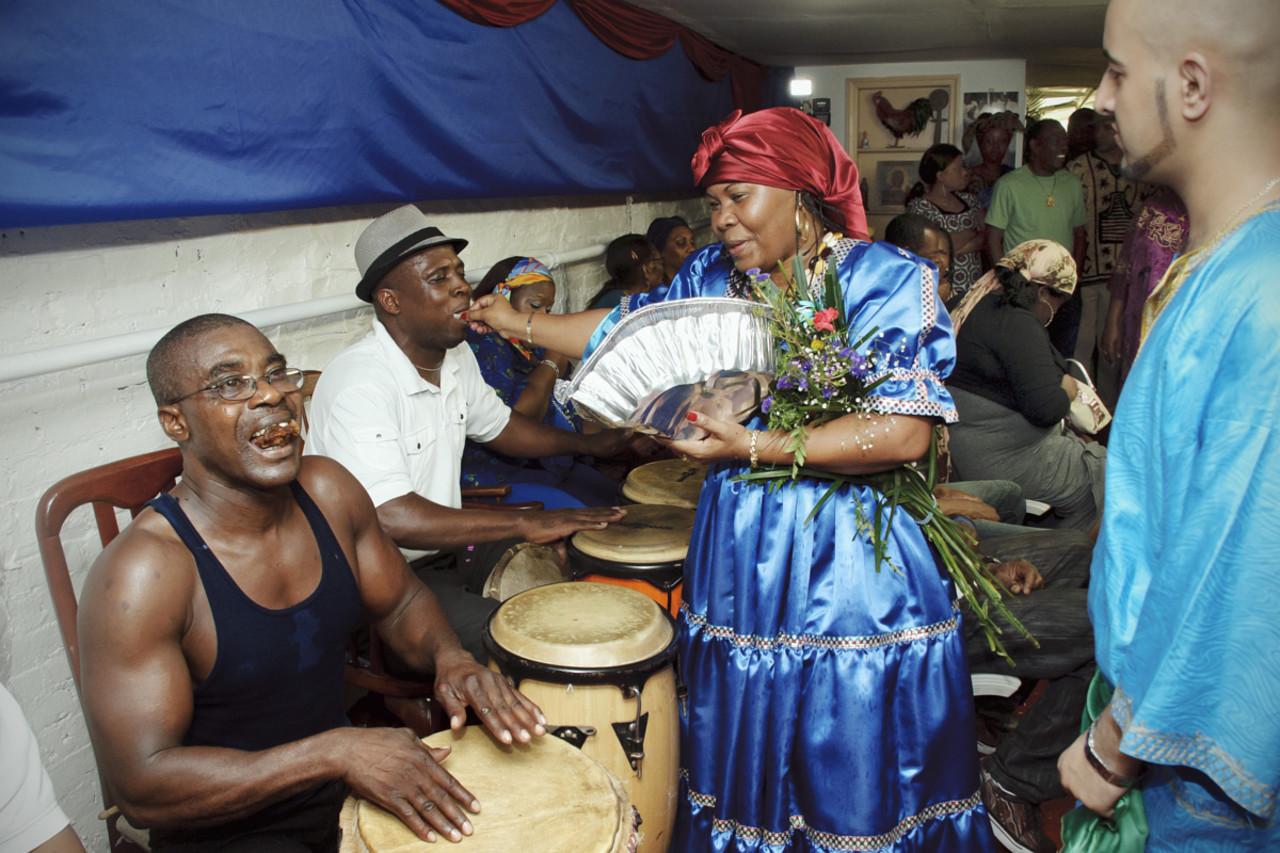 Supote Bon Mambo is possessed by Erzulie Dantor, who is feeding the drummers; behind her, Oungan Ahmed translates the energy from the spirit (Photo courtesy Shannon Taggart)