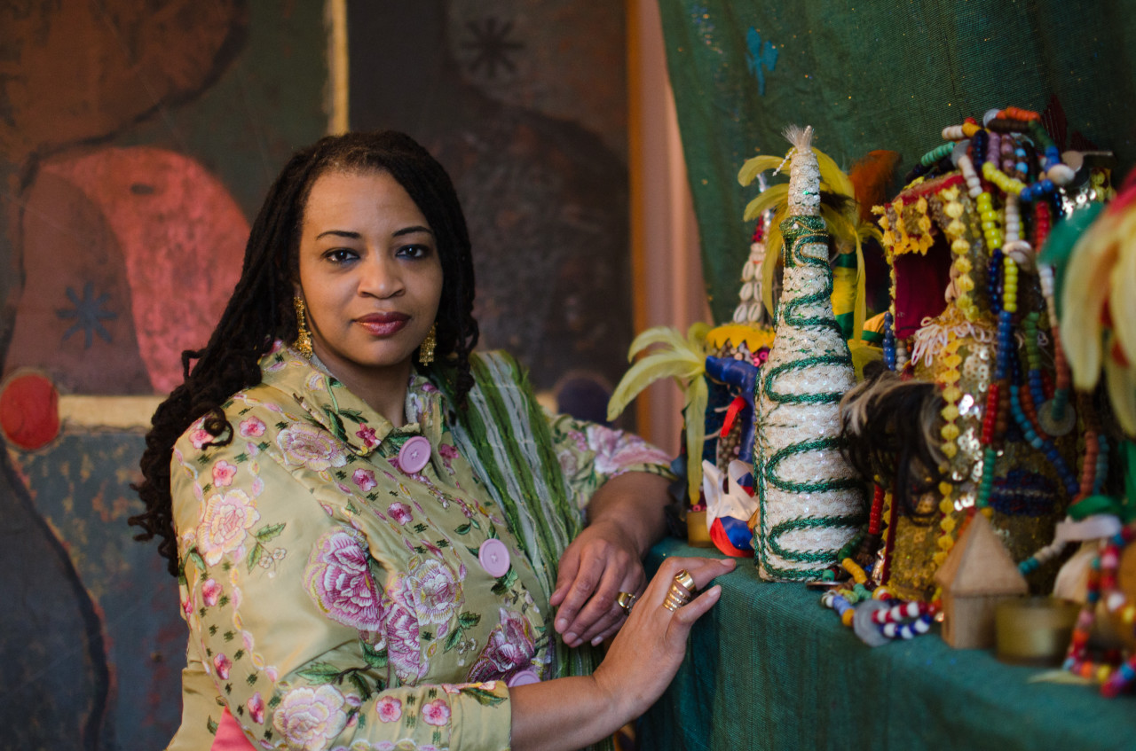 Dowoti Desir stands in front of a makeshift Vodou shrine in her Harlem home