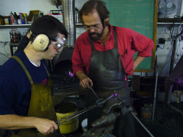 Nader getting a lesson from blacksmithing teacher Carl at Prospect Hill Forge
