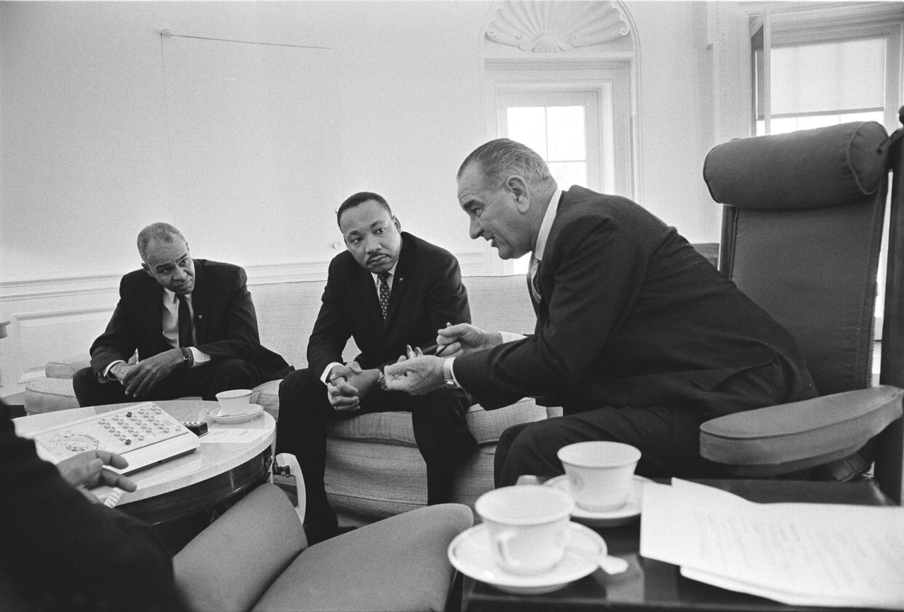 President Johnson leans in while conversing with Rev. King, Roy Wilkins, and other civil rights leaders in the Oval Office; January, 1964. (White House photo by Yoichi Okamoto, via LBJ Library)