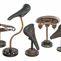 Group-of-5-vintage-bicycle-seats-mounted-on-rustic-stands-s