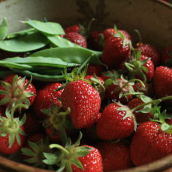 A bowl full of strawberries with a side of peas
