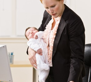 Businesswoman holding baby at desk