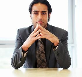 pensive businessman sitting at office desk