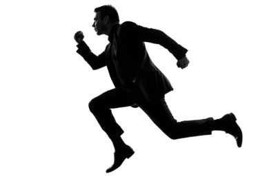 one caucasian business man running in silhouette  on white backg