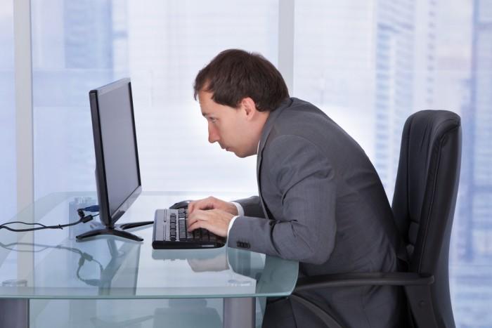leaning over desk