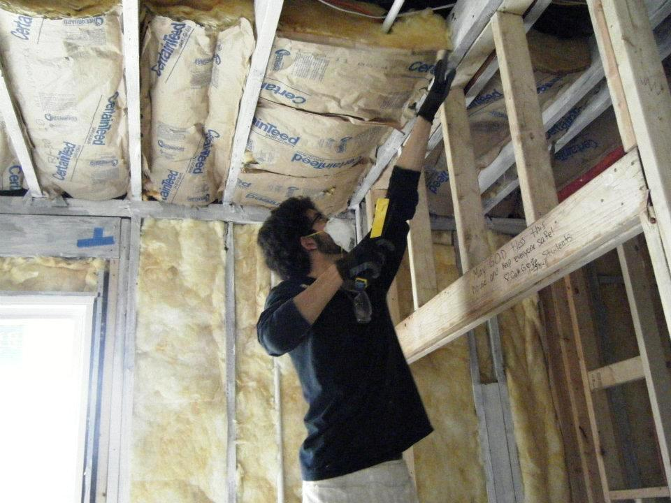 Carlos installing insulation to the house his Santa Clara University group helped rebuild in New Orleans.