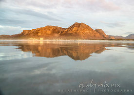 Muizenberg Peak reflected in the water at Muizenberg Beach, sunrise