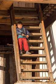 A local boy standing on the stairs of a house in Phobjikha valley, Bhutan.
